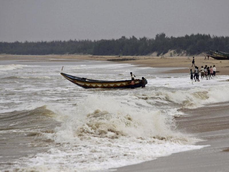 Fishermen pull out a country boat from the Bay of Bengal at Gokhurkuda in Ganjam district, Odisha following a cyclone alert. (AP photo)