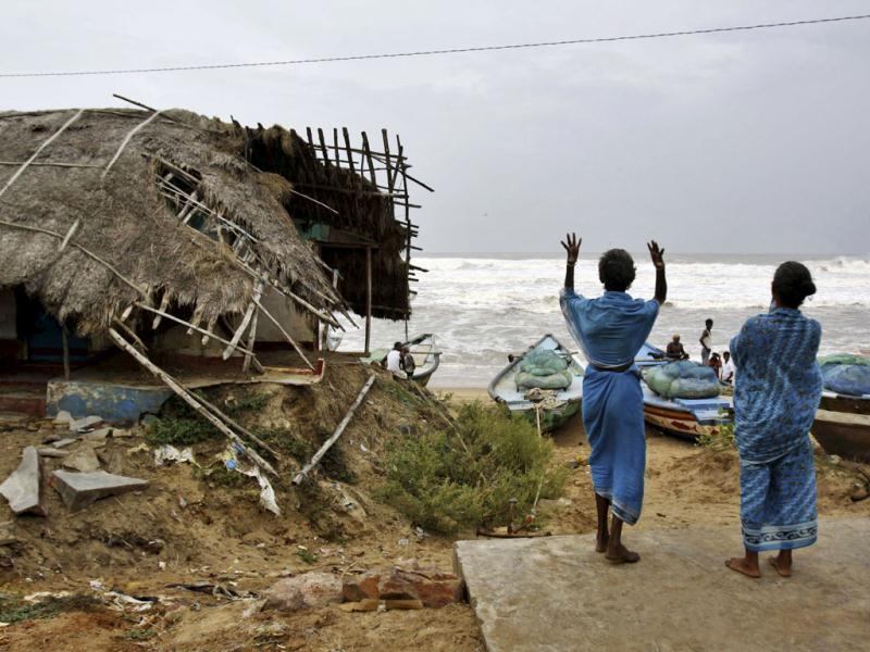 Women indicate to fishermen to return following a cyclone alert before evacuating their village in Gokhurkuda in Ganjam district, Odisha. (AP photo)