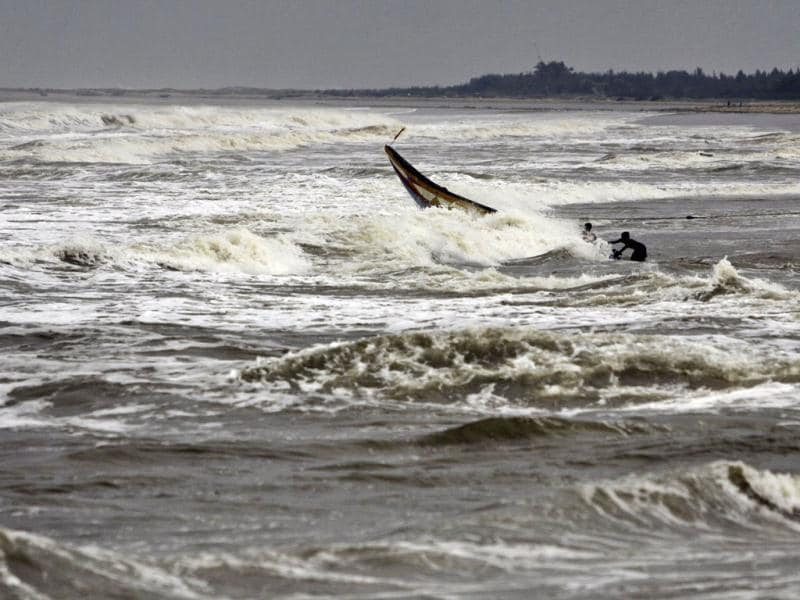 Fishermen try to balance their boat as they pull it out from the Bay of Bengal in Ganjam district, Odisha following a cyclone alert.(AP photo)