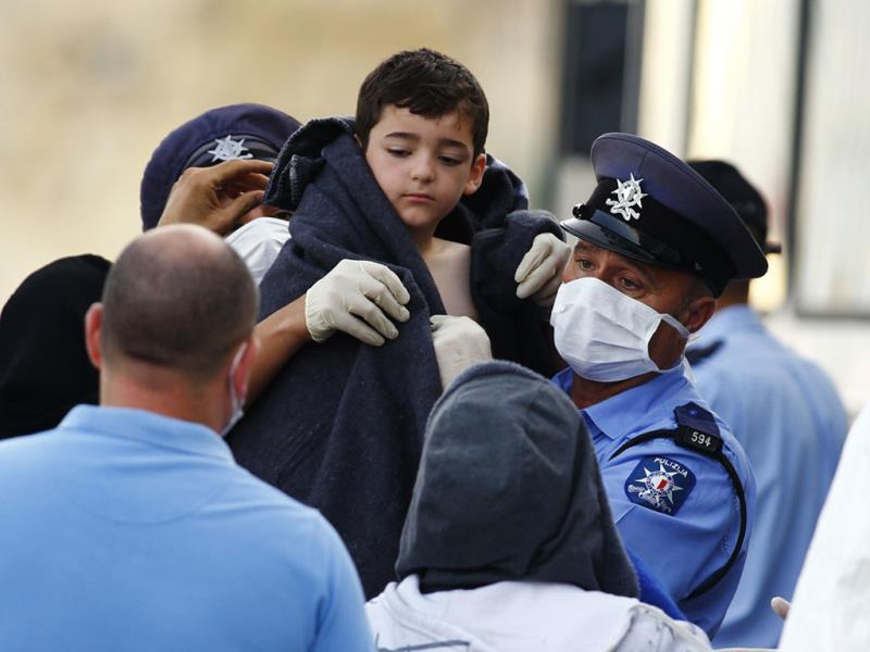 Police officers wrap a blanket around a rescued migrant child at the Armed Forces of Malta Maritime Squadron base at Haywharf in Valletta's Marsamxett Harbour. (Reuters Photo)