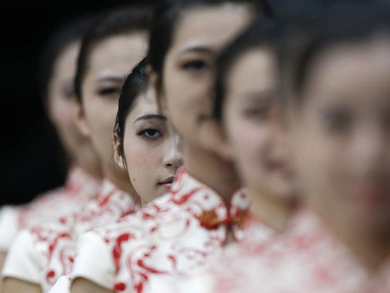 Ceremony hostesses line up waiting to present medals to winning athletes after artistic gymnastics women's team final at the sixth East Asian Games in Tianjin, China, Saturday, Oct. 12, 2013. Chinese team won gold medals. (AP Photo)