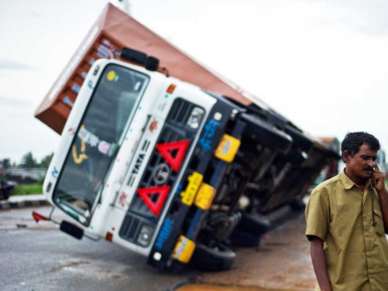 A truck driver speaks on his phone after his truck carrying Toyota cars was overturned by strong winds Andhra Pradesh-Odisha National Highway. (AFP Photo)