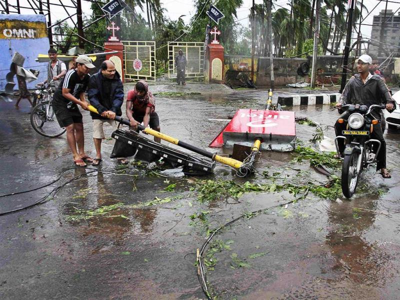 Locals remove a traffic signal pole fallen during Cyclone Phailin from a road in Berhampur. (AP Photo)