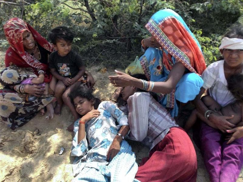 Family members of the injured beside them, after a stampede at the Sindhu River bridge through which pilgrims were heading towards the Ratangarh temple in Datia district of Madhya Pradesh on Sunday morning. (PTI Photo)