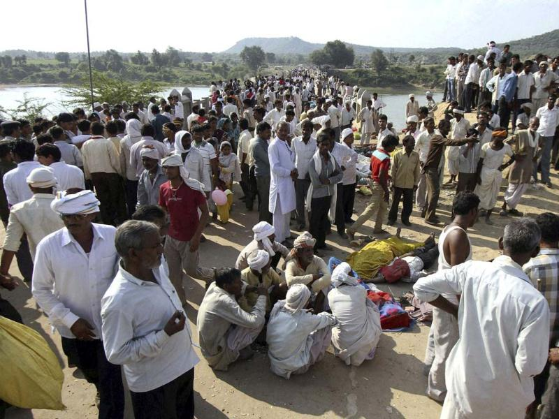 Villagers gather after a deadly stampede on a bridge across the Sindh River in Datia district in Madhya Pradesh state. (AP Photo)