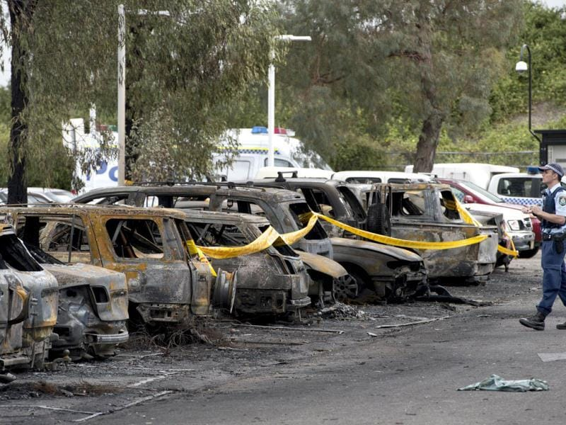 A police officer walks next to burnt vehicles following a fire at Sydney's Olympic Park. Eighty cars were destroyed in a devastating fire at Sydney's Olympic Park.(AFP photo)