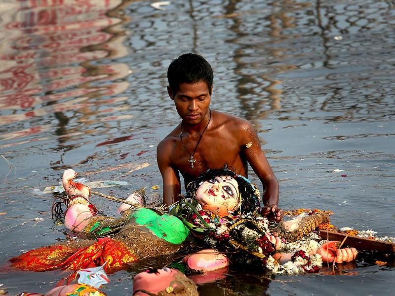 A devotee submerges an idol of Hindu goddess Durga in the river Yamuna at the end of the Durga Puja festival, in New Delhi. AP Photo