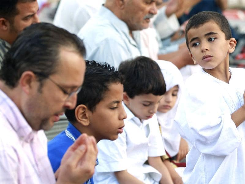 A boy prays during Eid al-Adha in Tunis to mark the end of the haj pilgrimage by slaughtering animals to commemorate Prophet Abraham's willingness to sacrifice his son, Ismail, on God's command. (Reuters photo)