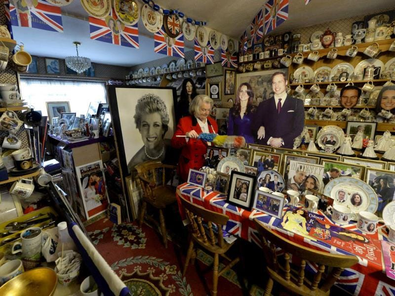 Margaret Tyler dusts some of the royal paraphernalia in the dining room of her home, which she has dedicated as a shrine to the British royal family. (Reuters Photo)