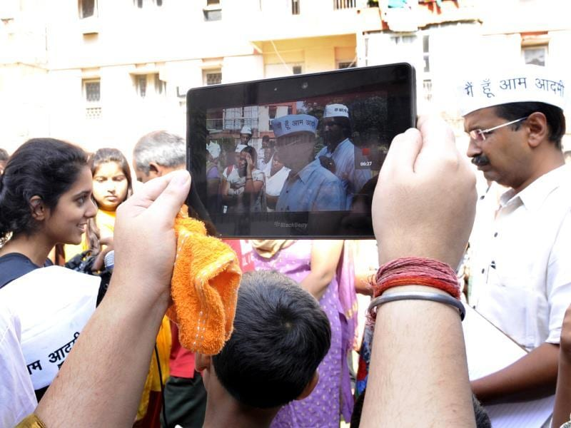 A woman takes a picture of Arvind Kejriwal while he interacts with residents of a multi-storey apartment in KG Marg in New Delhi. (HT Photo/ Sunil Saxena)