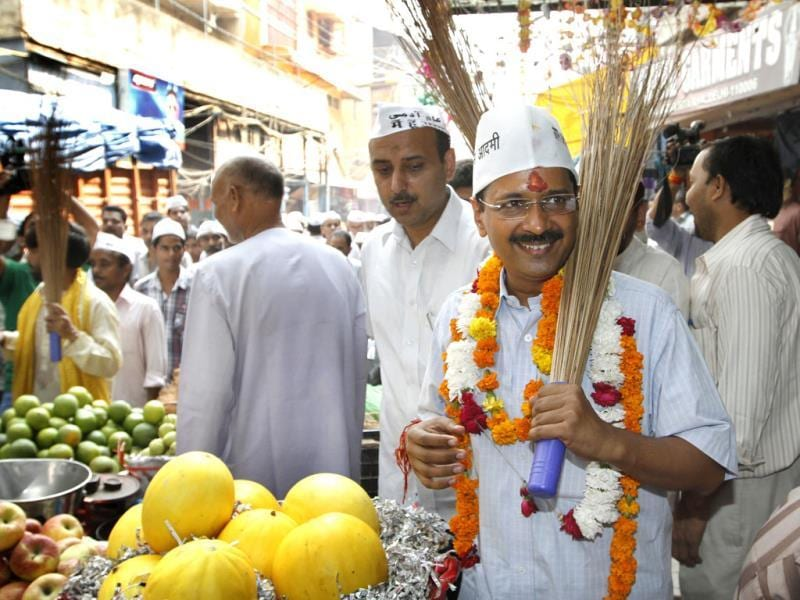 Aam Aadmi Party leader Arvind Kejriwal flashes their party symbol 'broom' during an election campaign near Jama Masjid in old Delhi. (HT Photo/Arvind Yadav)