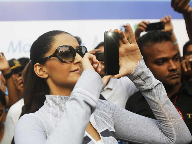 A very health concious Kapoor takes pictures from her cellphone during the event. (AP Photo)