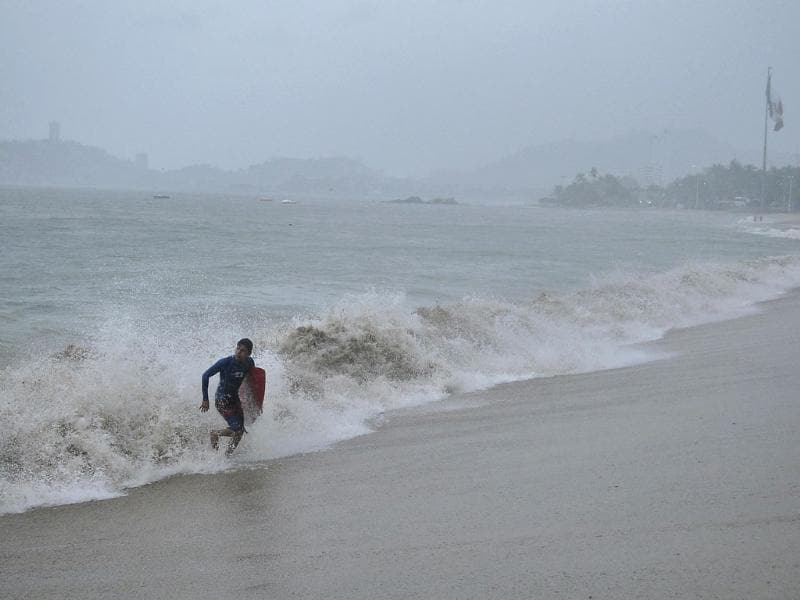 A surfer runs off a beach during rainfall brought on by Hurricane Raymond in Acapulco. Raymond, a category three hurricane, weakened slightly on Monday night. (Reuters Photo)