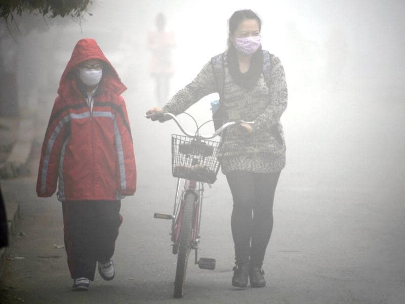 A woman walks with her child on a street as schools were closed due to the heavy smog in Jilin, northeast China's Jilin province. (AFP Photo)