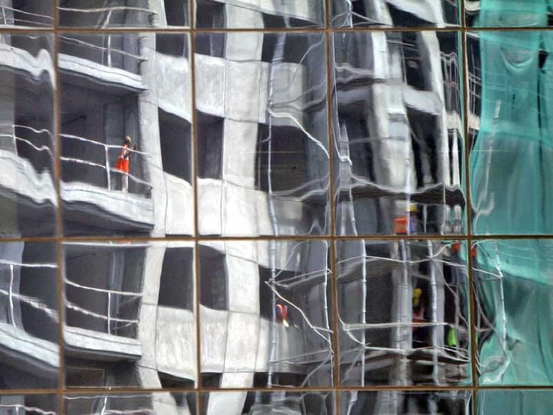 An under-construction building is reflected on the glass facades of a commercial complex in Chennai. (Reuters Photo)