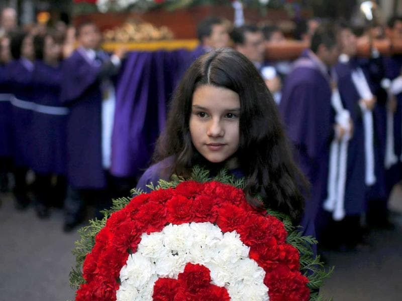 A girl carries a Peruvian wreath made of flowers as she participates in a procession in Madrid, Spain. (AP Photo)