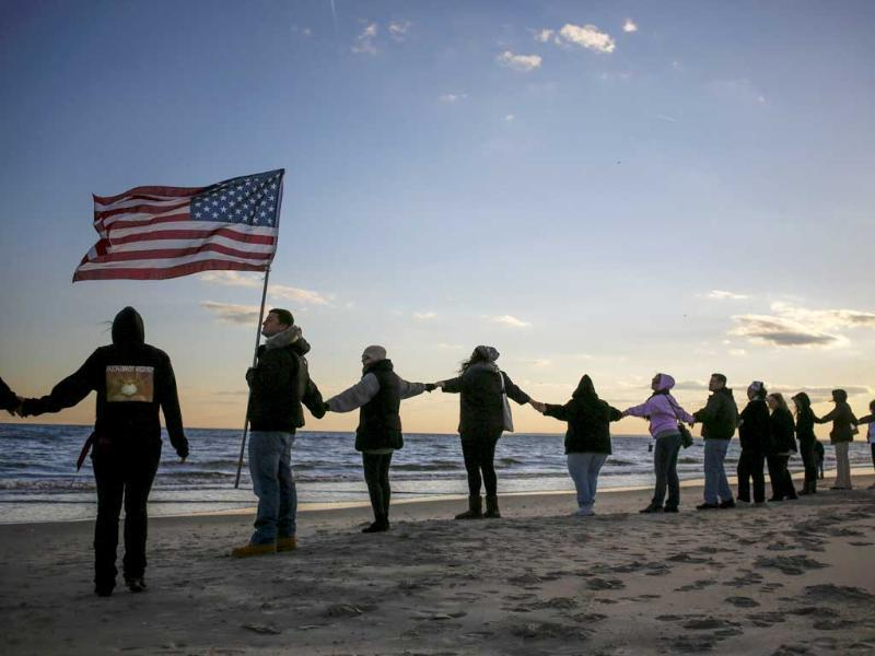 People hold hands during a remembrance ceremony along the beachfront damaged by hurricane Sandy in October 2012 in New York. (Reuters Photo)