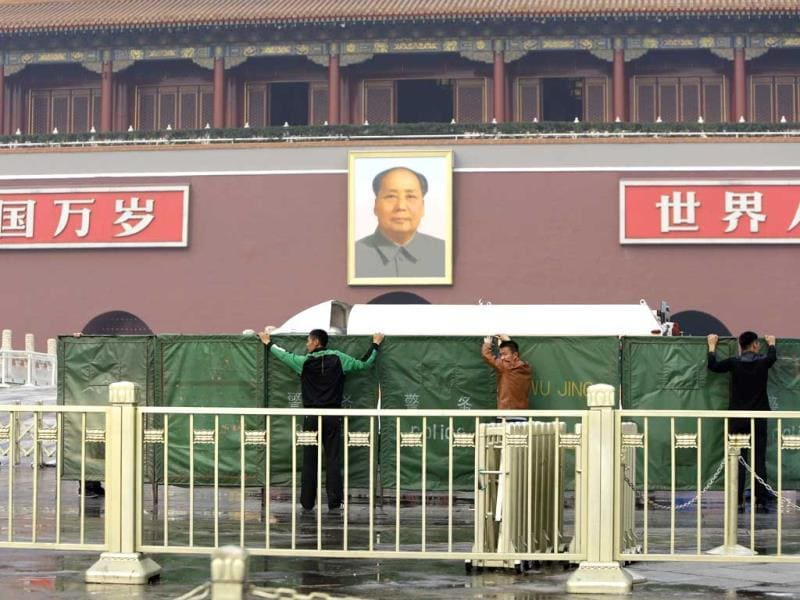 Police officers set up barriers in front of the giant portrait of the late Chinese Chairman Mao Zedong as they clean up after a car accident at the Tiananmen Square in Beijing (Reuters)