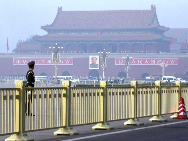 Paramilitary policemen guard and patrol Tiananmen Square, near Tiananmen Gate, back, where a vehicle veered into a crowd, in Beijing (AP Photo)