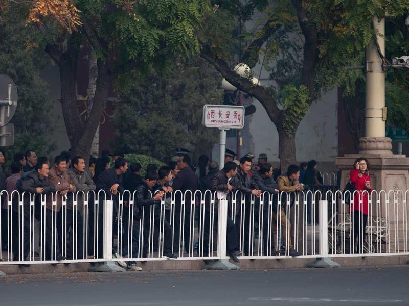 Tourists watch after they were barred from walking towards Tiananmen Gate following a car fire near the gate in Beijing, where a vehicle veered into a crowd in front of Beijing's Forbidden City andcrashed and caught fire, killig three. (AP Photo)