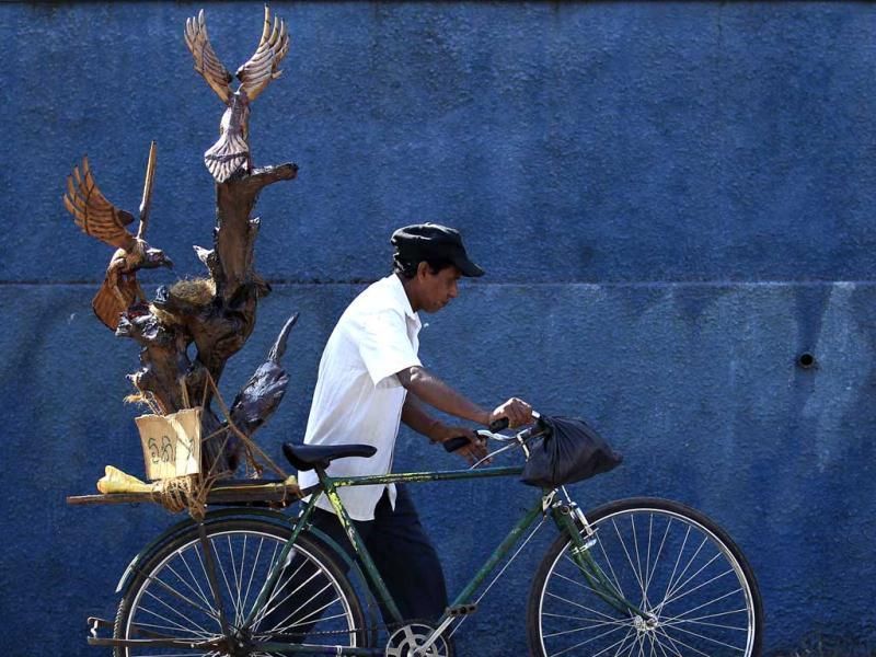 A carpenter transports a wooden sculpture on his bicycle in Colombo. (Reuters Photo)