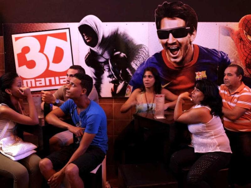 People wait to see a movie next to a image of Barcelona soccer player Lionel Messi at a private movie theater called 3D Mania in Havana. (AP Photo)