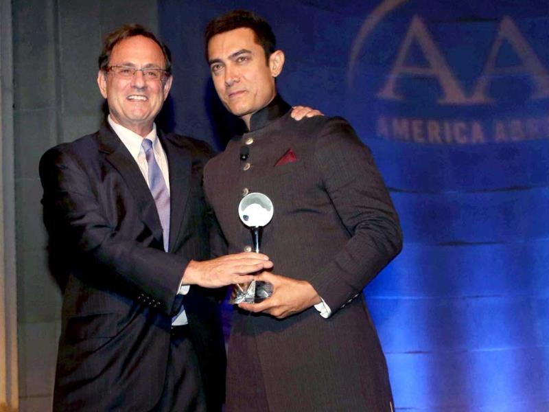 Former Assistant Secretary of Defence for Public Affairs, Douglas B Wilson, honours Bollywood actor Aamir Khan at America Abroad Media's 2013 Inaugural Awards Gala Dinner in Washington on Monday. PTI
