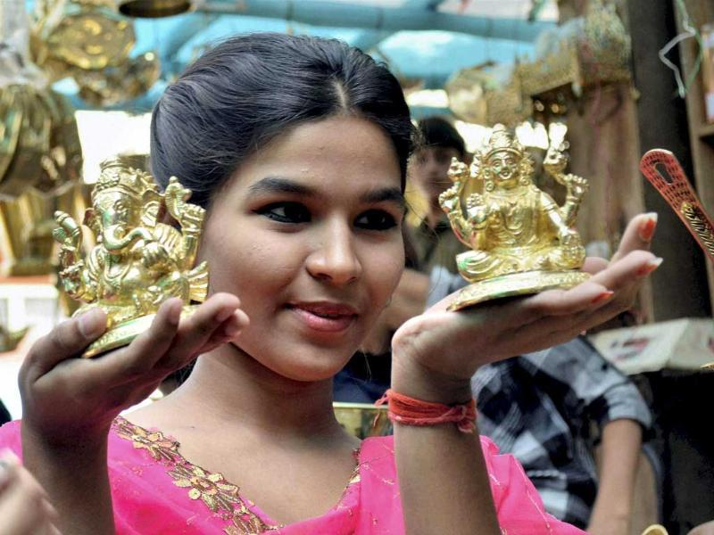 A girl showing metal statues of lord Ganesh and goddess Laxmi at a shop on the occasion of Dhanteras festival in Patna. (PTI Photo)