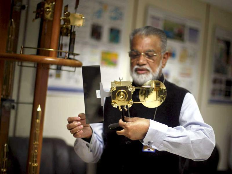 Isro chairman K Radhakrishnan holds a model of Mars orbiter at his office in New Delhi. (AP photo)