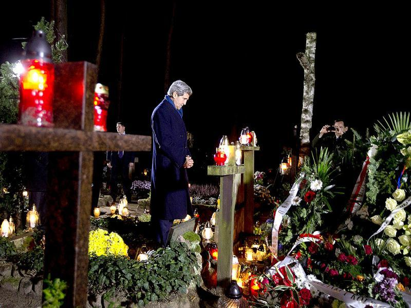 US Secretary of State John Kerry pays his respects as he visits the gravesite of Poland's former Prime Minister Tadeusz Mazowiecki, Eastern European first democratic Prime Minister after communism, in Laski, Poland. (AFP Photo)