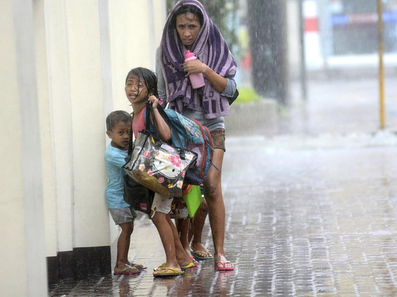 A mother takes refuge with her children as Typhoon Haiyan hits Cebu city, central Philippines. Typhoon Haiyan, the strongest typhoon in the world this year and possibly the most powerful ever to hit land battered the central Philippines on Friday, forcing millions of people to flee to safer ground, cutting power lines and blowing apart houses. (Reuters)
