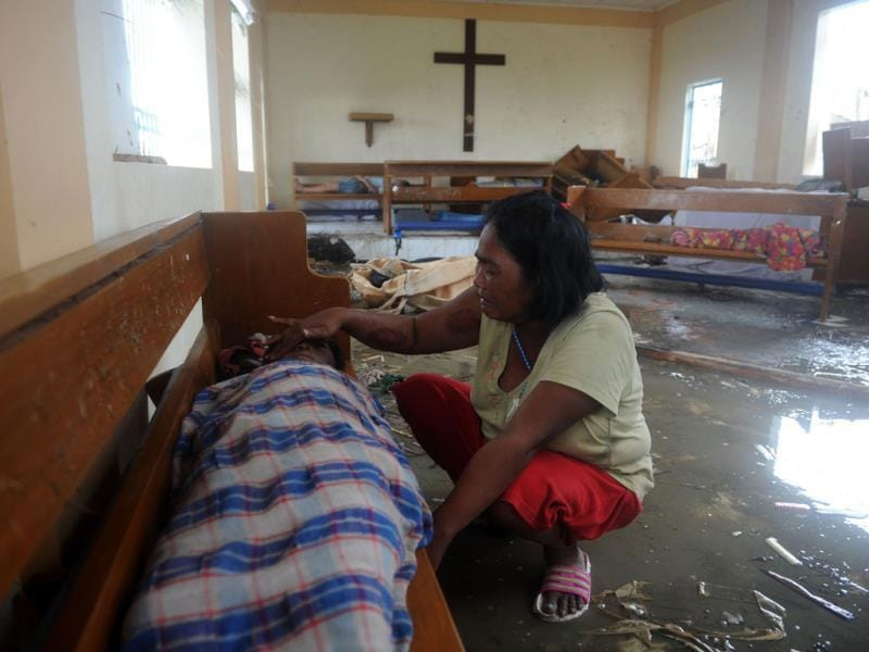A mother weeps beside the dead body of her son at a chapel in the aftermath of Super Typhoon Haiyan in Tacloban, eastern island of Leyte. More than 100 bodies were lying in the streets of a Philippine city smashed by Super Typhoon Haiyan, authorities said, as soldiers raced to reach many other devastated communities. (AFP photo)