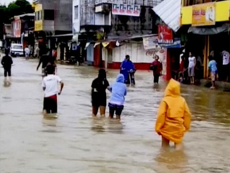 In this image made from ABS-CBN video, residents wade through a flooded street caused typhoon Haiyan, in Mindoro, Philippines. Typhoon Haiyan, one of the strongest storms on record, has killed more than 100 people and injured another 100 in the central Philippines as it wiped away buildings and leveled seaside homes before sweeping west toward Vietnam, still packing destructive winds. (AP Photo)