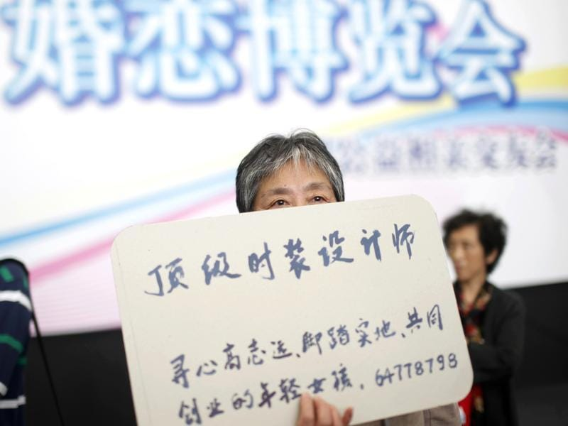 A woman holds the information card of her bachelor family member during a mass match-making event ahead of Singles Day in Shanghai, China. (AP Photo)