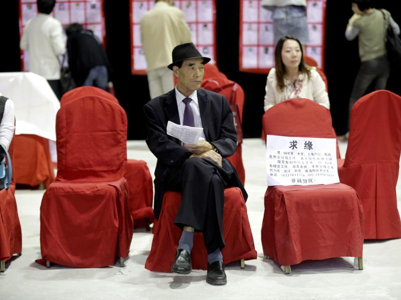 A man sits with the information card of his bachelor family member during a mass match-making event ahead of Singles Day in Shanghai, China. (AP Photo)