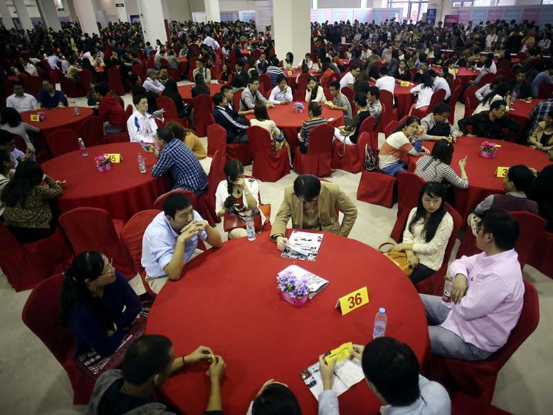 Bachelor participants exchange their information during a mass match-making event ahead of Singles Day in Shanghai, China. (AP Photo)