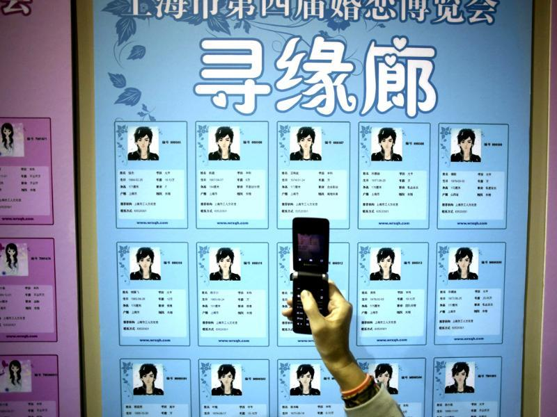 A participant takes a photo of the information cards of bachelors on the wall during a mass match-making event ahead of Singles Day in Shanghai, China. (AP Photo)