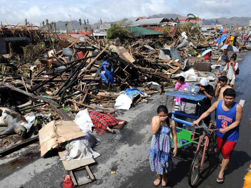Residents walk past destroyed houses and dead bodies littered along a road in Tacloban, on the eastern island of Leyte on sunday.(AFP PHOTO)