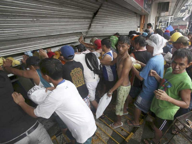 Residents push a shutter to open a small grocery to get food in Tacloban city, Leyte province central Philippines on Sunday. (AFP PHOTO)