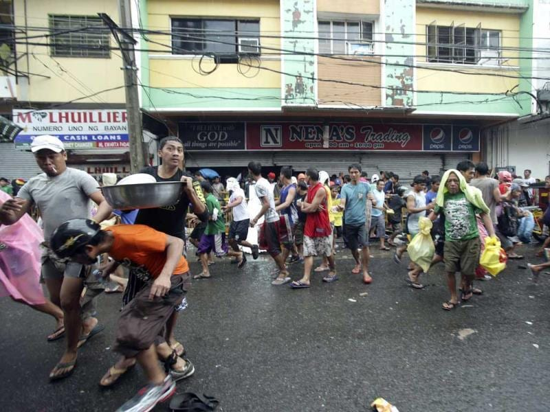 Residents run out carrying food after storming a grocery shop in Tacloban city, Leyte province central Philippines on Sunday.(AP PHOTO)
