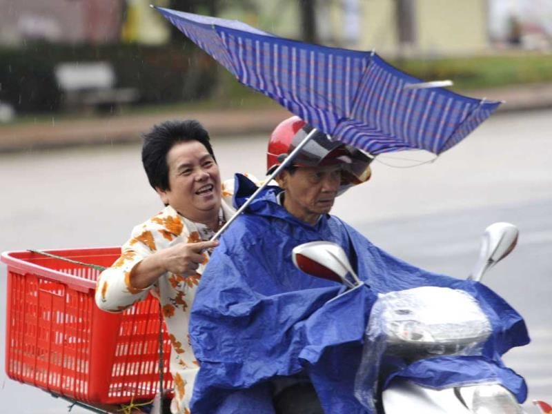 People ride against rain and wind under the influence of Typhoon Haiyan, in Qionghai, south China's Hainan province on sunday.(REUTERS PHOTO)
