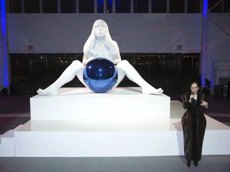 Lady Gaga poses with a sculpture of her by artist Jeff Koons at the 'artRave' release event of her new album 'ARTPOP