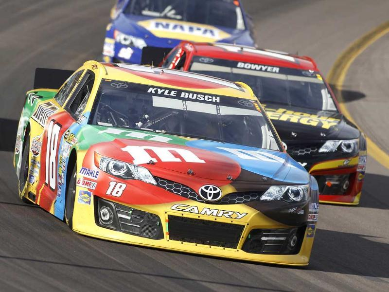 Driver Kyle Busch races out of turn two in front of Clint Bowyer during the AdvoCare 500 Nascar Sprint Cup Series auto race at Phoenix International Raceway in Avondale. (AP photo)