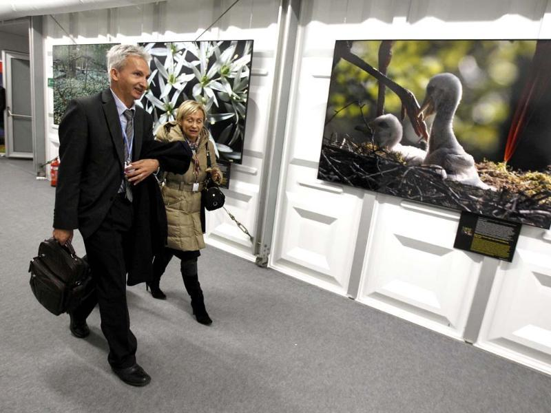 Delegates walk in front of pictures, part of exhibition