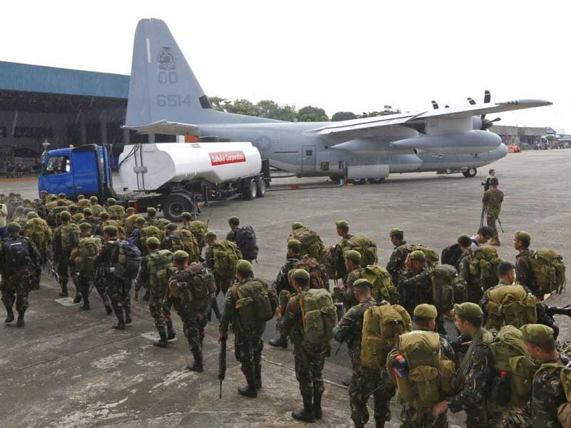 Philippine soldiers walk near a military C-130 plane as they prepare to go to Tacloban city, at the Villamor Airbase, in Manila, Philippines. (AP Photo)