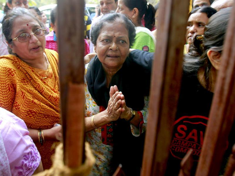 A resident of Mumbai's Campa Cola housing colony folds her hands and pleads for her home not to be demolished, as residents block the gate in Mumbai. AP/Rafiq Maqbool