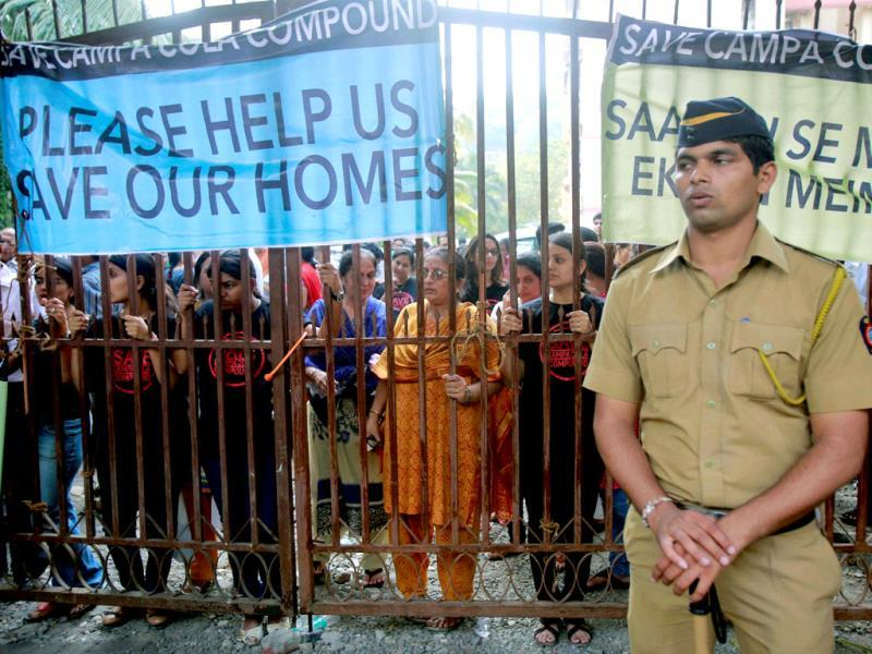 A policeman stands in front of a gate blocked by residents of Mumbai's Campa Cola housing colony in Mumbai. PTI