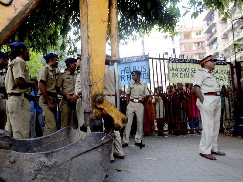 Policemen stand near an earthmover as residents of Mumbai's Campa Cola housing colony block the entrance to their colony in Mumbai. PTI