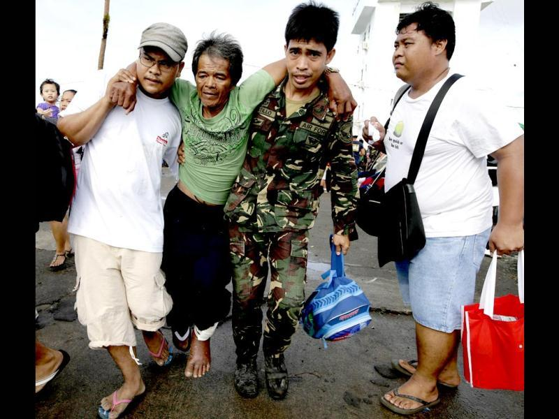 A typhoon survivor is assisted by a relative and a soldier to board a military transport plane from the damaged Tacloban airport in Tacloban city, Leyte province in central Philippines. (AP Photo)