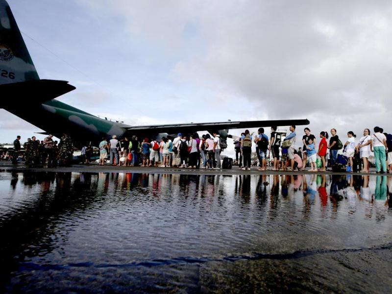 Typhoon survivors prepare to board a military transport plane from the damaged Tacloban airport in Tacloban city, Leyte province in central Philippines. (AP Photo)